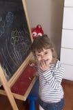 乱写在花图画的小女孩在黑板的 免版税库存照片