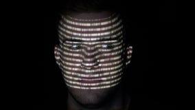 乱砍白色二进制编码字符的一个美好的计算机程序设计者的画象在他的面孔被反射- 股票录像