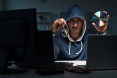 乱砍计算机的黑客在晚上 图库摄影