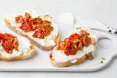 乳清干酪和各式各样的蕃茄三明治在白板 库存照片