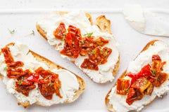 乳清干酪和各式各样的蕃茄三明治在白板 免版税图库摄影