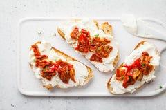 乳清干酪和各式各样的蕃茄三明治在白板 库存图片