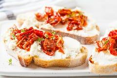 乳清干酪和各式各样的蕃茄三明治在白板 免版税库存照片