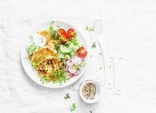 乳清干酪夏南瓜油炸馅饼和新鲜蔬菜沙拉 黄瓜、西红柿、萝卜、微绿色和夏南瓜薄煎饼 库存照片