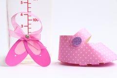 乳瓶和桃红色鞋子 免版税图库摄影