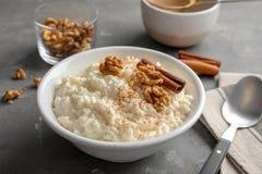 乳脂状的大米布丁用桂香和核桃在桌上服务的碗 免版税图库摄影