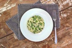 乳脂状的意大利煨饭用豌豆和菠菜在白色板材在灰色布料在土气桌上 图库摄影