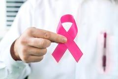 乳腺癌了悟概念 拿着桃红色丝带的医生 免版税库存图片