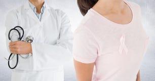 乳腺癌医生和妇女有桃红色了悟丝带的 库存图片