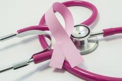 乳腺癌的概念 在胸部检查的桃红色紫色听诊器医生的附近桃红色丝带,象征诊断, trea 库存照片
