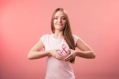 乳腺癌治疗战斗查找资金邮政印花税 做心脏形状的妇女在桃红色丝带 免版税库存照片