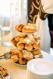 乳蛋糕板材从三个地板立场的在自助餐桌上 免版税图库摄影