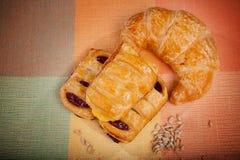 乳蛋糕蛋糕和新月形面包面包 免版税图库摄影