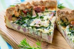 乳蛋饼洛林,饼用一把熏制的烟肉、乳酪和菠菜 免版税库存图片