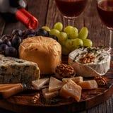 乳酪、坚果、葡萄和红葡萄酒在木背景 免版税图库摄影