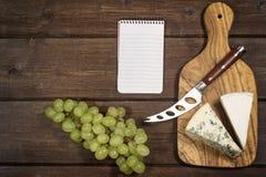 乳酪、葡萄和纸笔记本 免版税库存图片