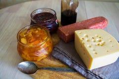 乳酪、蒜味咸腊肠和瓶子大片断用果酱 免版税库存照片
