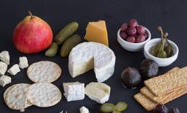 乳酪、薄脆饼干、腌汁和果子在黑背景 免版税库存照片