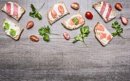 乳酪三明治用在一条分支和草本西红柿和三文鱼的蕃茄在木土气背景顶视图边界, pla 库存图片