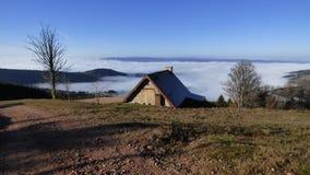 乳酪制造商小屋在云彩上的在col des supeyres,奥韦涅,法国 免版税库存图片