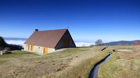 乳酪制造商小屋在云彩上的在col des supeyres,奥韦涅,法国 库存照片