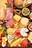 乳酪和开胃菜的各种各样的类型板被设置的 库存图片