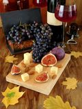 乳酪和无花果在一个木板和成熟葡萄 免版税库存图片