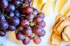 乳酪和葡萄在板材 免版税图库摄影