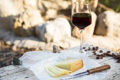 乳酪和葡萄干片断与一块红葡萄酒玻璃在老木头 免版税图库摄影