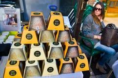乳酪圆锥形头堆积在金字塔和被包装入白色和黄色纸盒 在框架左边在背景Phot中 免版税库存图片