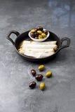 乳酪在土气背景滚动板材用在一个黑平底锅供食的橄榄 免版税库存照片