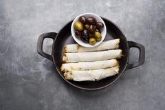 乳酪在土气背景滚动板材用在一个黑平底锅供食的橄榄 免版税图库摄影