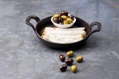 乳酪在土气背景滚动板材用在一个黑平底锅供食的橄榄 免版税库存图片