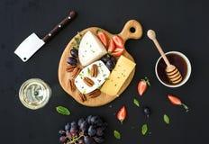 乳酪开胃菜选择或呜咽声快餐集合 乳酪、葡萄、山核桃果、草莓和蜂蜜品种  免版税库存照片