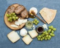 乳酪开胃菜选择或酒快餐集合 意大利乳酪、绿色葡萄、面包切片和蜂蜜品种在圆 图库摄影