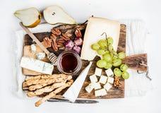 乳酪开胃菜集合 乳酪、蜂蜜、葡萄、梨、坚果和面包grissini棍子的各种各样的类型在土气木 免版税库存图片