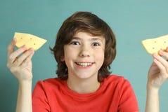 乳酪微笑青春期前的男孩说有两个乳酪切片的 库存照片