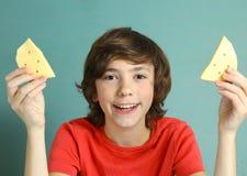 乳酪微笑青春期前的男孩说有两个乳酪切片的 图库摄影