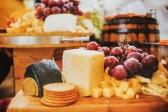 乳酪板和葡萄,蒜味咸腊肠和薄脆饼干,在木和土气背景在墨西哥城 免版税库存图片