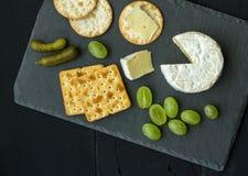 乳酪板用咸味干乳酪、葡萄、腌汁和薄脆饼干在黑sl 库存照片