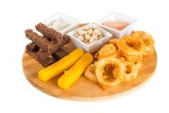 乳酪棍子、洋葱圈、薄脆饼干、盐味花生和调味汁 免版税图库摄影