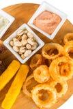 乳酪棍子、洋葱圈、薄脆饼干、盐味花生和调味汁 库存照片
