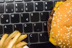 乳酪汉堡和炸薯条在膝上型计算机键盘-快餐午餐在工作场所 库存图片