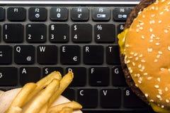 乳酪汉堡和炸薯条在膝上型计算机键盘-快餐午餐在工作场所 库存照片