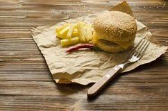 乳酪汉堡用在一张工艺纸的油煎的土豆在木bac 免版税图库摄影