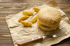 乳酪汉堡用在乡村模式的油煎的土豆在工艺 库存图片
