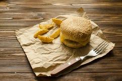 乳酪汉堡用在乡村模式的油煎的土豆在工艺p 图库摄影