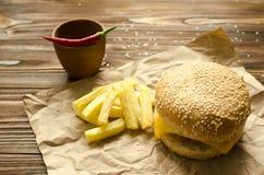 乳酪汉堡用在乡村模式的油煎的土豆在工艺p 库存照片