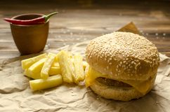 乳酪汉堡用油煎的土豆和辣味番茄酱在工艺pa 免版税库存图片