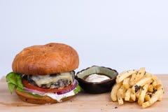 乳酪汉堡用炸薯条和垂度在木板,白色b 免版税库存照片